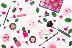 Scrittorio alla moda con i cosmetici della donna e le rose rosa su fondo bianco Disposizione piana, vista superiore Fondo di bell fotografie stock libere da diritti