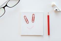 Scrittorio bianco con il blocco di carta, un sorriso tirato su  fotografia stock