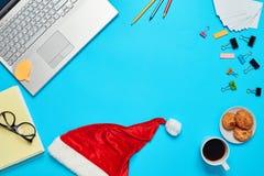 Scrittorio blu con il computer portatile, il coffe degli elementi dell'ufficio e la tazza di Santa Fotografia Stock