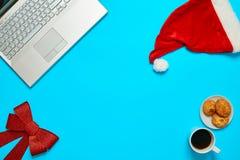 Scrittorio blu con il computer portatile, il coffe degli elementi dell'ufficio e la tazza di Santa Immagine Stock Libera da Diritti