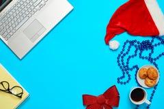 Scrittorio blu con il computer portatile, il coffe degli elementi dell'ufficio e la tazza di Santa Fotografie Stock