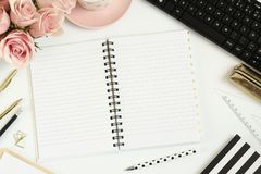 Scrittorio con i fiori rosa, il taccuino vuoto ed il computer fotografie stock