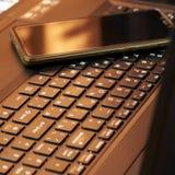 Scrittorio con il computer portatile, lo Smart Phone, i taccuini, le penne, gli occhiali e una tazza di tè Vista di angolo latera fotografie stock libere da diritti