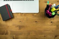 Scrittorio con il computer portatile, un taccuino nero e un supporto pieno della penna immagine stock libera da diritti