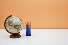 Scrittorio degli allievi con il globo e le matite Fotografia Stock
