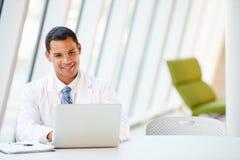 Scrittorio del dottore Using Laptop Sitting At in ospedale moderno fotografie stock