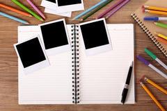 Scrittorio dello studente di college con l'album di foto in bianco e parecchie stampe della polaroid Fotografie Stock Libere da Diritti