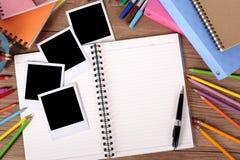 Scrittorio dello studente di college con l'album di foto in bianco e parecchie stampe della polaroid Fotografia Stock