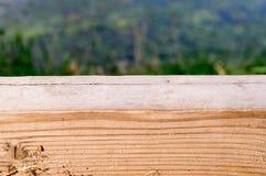 Scrittorio di legno con fondo vago di paesaggio con erba Fotografia Stock