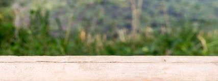 Scrittorio di legno con fondo vago di paesaggio con erba Immagini Stock Libere da Diritti