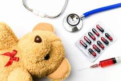 Scrittorio di medico con attrezzatura medica e l'orsacchiotto marrone Immagine Stock