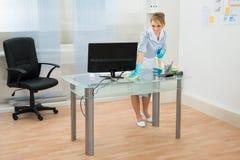 Scrittorio di pulizia della domestica in ufficio immagine stock