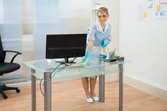 Scrittorio di pulizia della domestica in ufficio Immagine Stock Libera da Diritti