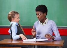 Scrittorio di Scolding Schoolgirl At dell'insegnante femminile Fotografia Stock Libera da Diritti