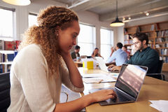 Scrittorio di Using Laptop At della donna di affari in ufficio occupato Immagine Stock