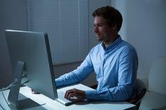 Scrittorio di Working Late At dell'uomo d'affari in ufficio immagini stock libere da diritti