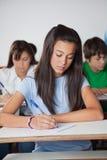 Scrittorio di Writing Paper At della studentessa in aula Fotografia Stock