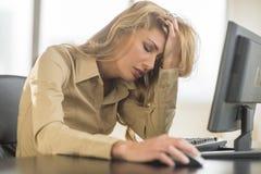 Scrittorio frustrato di Leaning On Computer della donna di affari fotografia stock libera da diritti
