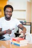 Scrittorio sorridente della biblioteca di Scanning Books At del bibliotecario Immagini Stock Libere da Diritti
