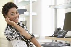Scrittorio sorridente di Sitting At Computer della donna di affari immagini stock libere da diritti