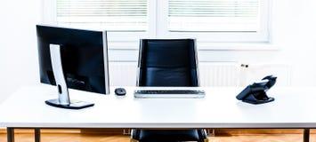 Scrittorio vuoto moderno dello spazio ufficio con il computer, il telefono e la sedia fotografia stock