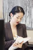 Scrittura abbastanza asiatica della donna di affari Immagine Stock Libera da Diritti