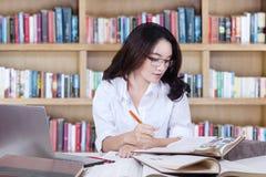 Scrittura abile dello studente della High School nella biblioteca Immagini Stock Libere da Diritti