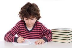 Scrittura adorabile del bambino nel banco Immagine Stock