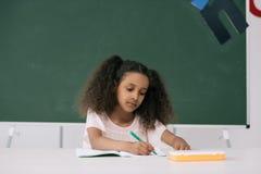 Scrittura afroamericana dell'allievo in quaderno alla lezione nella classe Immagine Stock Libera da Diritti