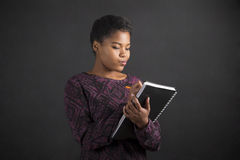 Scrittura afroamericana della donna in diario del libro sul fondo della lavagna fotografia stock libera da diritti