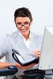 Scrittura ambiziosa della donna di affari nel suo ordine del giorno Fotografia Stock Libera da Diritti
