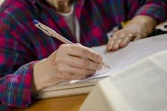 Scrittura anziana della donna Immagini Stock Libere da Diritti