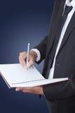 Scrittura asiatica dell'uomo d'affari sul taccuino. Immagini Stock