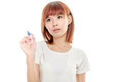 Scrittura asiatica della donna con l'indicatore blu sul bordo immaginario Fotografia Stock