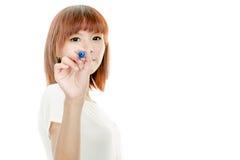 Scrittura asiatica della donna con l'indicatore blu sul bordo immaginario Fotografie Stock