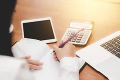 Scrittura asiatica della donna di affari sul taccuino sulla tavola con il calcolatore e la compressa del computer portatile Immagine Stock