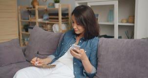 Scrittura astuta della donna in taccuino facendo uso della seduta sorridente dello smartphone sul sofà a casa archivi video