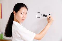 Scrittura cinese della ragazza della High School a bordo Immagini Stock