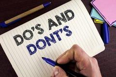 Scrittura concettuale della mano che mostra Do ed i Don'Ts Montrare della foto di affari che cosa può essere fatto e che cosa non immagini stock