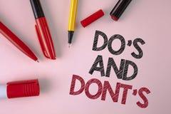 Scrittura concettuale della mano che mostra Do ed i Don'Ts Testo della foto di affari che cosa può essere fatto e che cosa non pu Immagine Stock