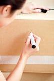 Scrittura contentissima della donna su una casella Fotografia Stock Libera da Diritti
