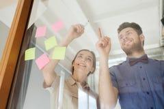 Scrittura creativa felice del gruppo sul vetro in bianco dell'ufficio Fotografie Stock