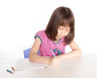 Scrittura del bambino allo scrittorio Immagine Stock Libera da Diritti