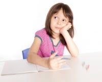 Scrittura del bambino allo scrittorio Fotografie Stock