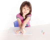 Scrittura del bambino allo scrittorio Fotografie Stock Libere da Diritti