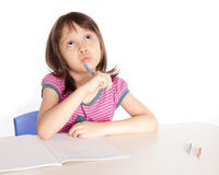 Scrittura del bambino e pensare allo scrittorio Fotografia Stock