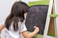 Scrittura del bambino sulla scrittura bambino/della lavagna sul fondo della lavagna Fotografia Stock