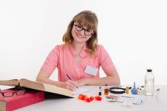 Scrittura del farmacista in taccuino che si siede ad una tavola Fotografie Stock