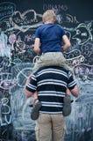 Scrittura del figlio e del padre sulla grande lavagna Immagini Stock Libere da Diritti