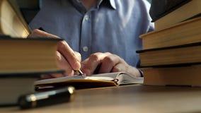 Scrittura del giovane nella biblioteca Libri dei mucchi su una tavola archivi video
